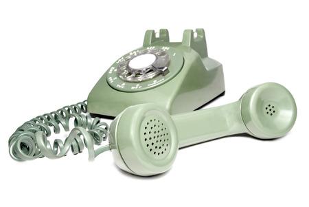 Photo de l'ancien téléphone rotatif vert rétro avec récepteur décroché sur un fond blanc. Banque d'images - 77879072