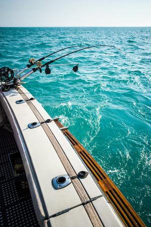 2 釣りポール リグの写真はターコイズ色の水と釣ボートと澄んだ空の背面にマウントされています。米国のミシガン湖の撮影。