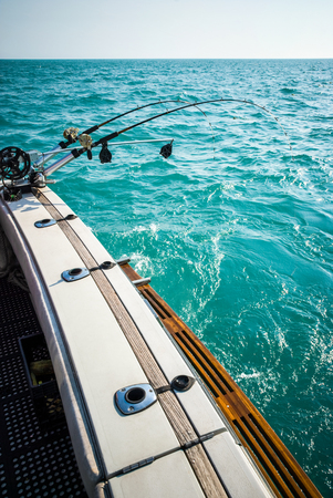 Picture of a two fishing pole rig mounted to the back of a sportfishing boat with turquoise colored water and a clear sky. Taken on Lake Michigan in the USA. Reklamní fotografie - 77879078