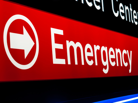 Hospital emergency sign in red and black and a directional arrow,