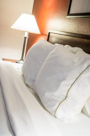 モダンなホテルの部屋のベッドの枕とランプ