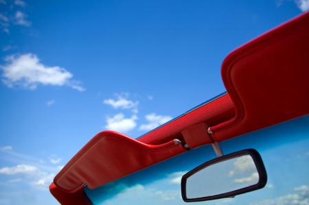 美しい青い空を見上げて、フロント ガラスを見ているトップダウンのコンバーチブル。
