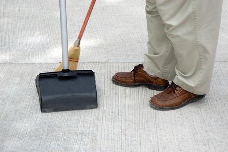 groundskeeper: Picture of person sweeping with a broom and dustpan Stock Photo