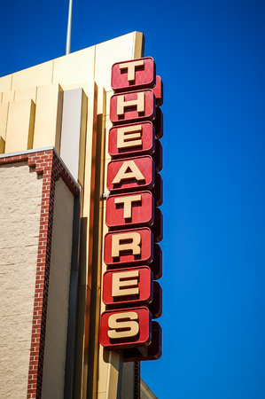Movie theatres marquee sign against a vivid blue sky