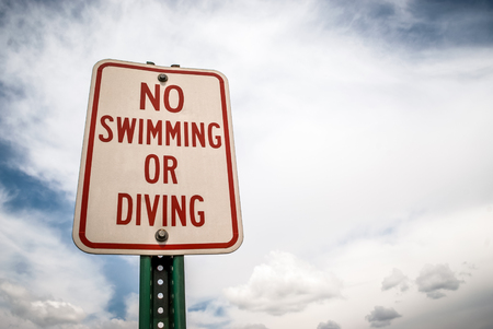 Stock picture of a no swimming or diving sign under a partly cloudy and blue sky.