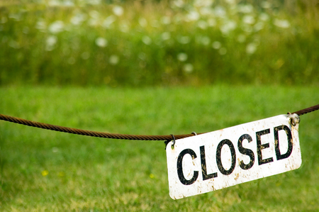 Closed sign hanging at the entrance of a nature forest preserve park.