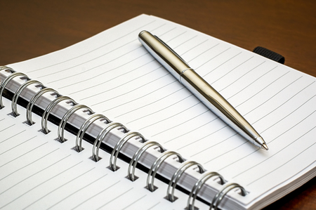 Picture of a silver pen and open spiral notebook lying on a dark brown wooden desk Reklamní fotografie