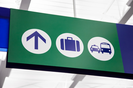 Picture of a directional airport sign with baggage claim and transporation symbols. Image Copyright © 2009 Paul Velgos with All Rights Reserved.