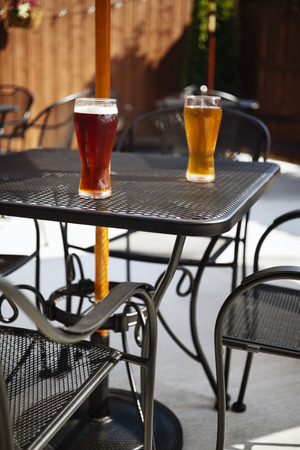 Two beer glasses with dark and light beer on an outdoor mesh bar patio table