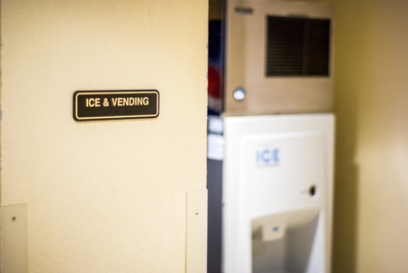 Picture of an Ice and Vending sign on a hotel wall with a slightly out of focus ice machine in the background.