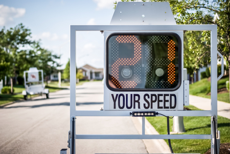 Picture of a mobile police speed radar trailer sign showing 21 mph sitting on a street in a suburban neighborhood. Reklamní fotografie - 77879127