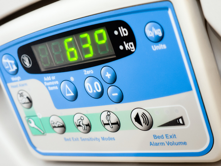 Hospital bed electronic weight scale that weighs patient while in bed