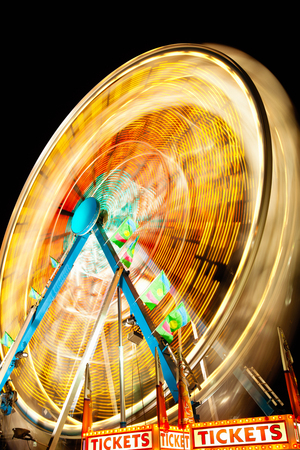 Picture of Carnival Ferris Wheel at night spinning motion blurred.