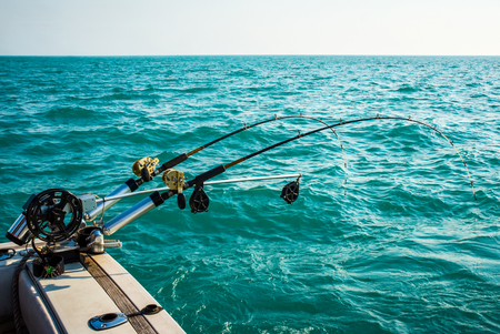 Picture of a two fishing pole rig mounted to the back of a sportfishing boat with turquoise colored water and a clear sky. Taken on Lake Michigan in the USA.