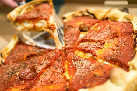ディープディッシュピザ引っ張られてスライスとチーズがぶら下がっています。著作権 © すべての権利予約とポール Velgos。