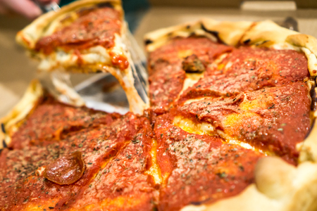 Deep Dish Pizza with a slice being pulled and cheese hanging. Copyright © Paul Velgos with All Rights Reserved.