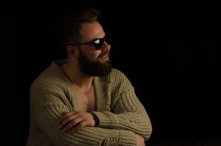 The young model posing in the studio is dressed in a cardigan and has bearded in his pockets and bearded .. sitting on a chair, looking forward and happy