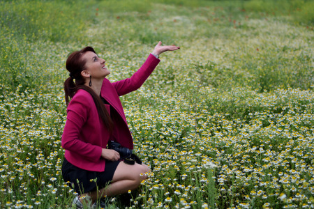 When the young photographer is in the field of chamomile the rain starts.happy and smiling.