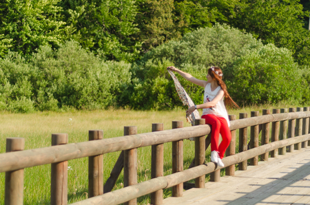 young woman with long hair, red pants, white shirt, flower crown in her hair sitting on wooden railings.Bullety on a spring day,