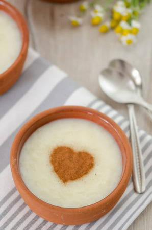 Rice pudding with cinnamon on wooden background Standard-Bild