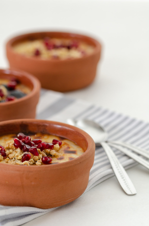 Traditional Turkish oven rice pudding and striped napkin on white backround.There are walnuts and pomegranate on the rice puding.