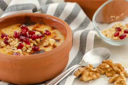 Traditional Turkish oven rice pudding..There are walnuts and pomegranate on the rice puding.Close-up Stok Fotoğraf