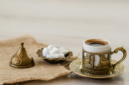 Oriental/Turkish coffee served in copper-plated pot with candies.