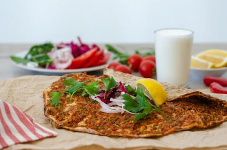 Turkish pizza with meat - lahmacun on a wooden table. Horizontal. Standard-Bild