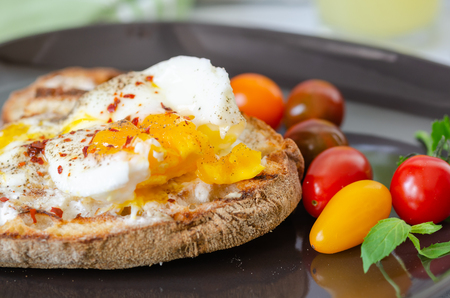 Turkish breakfast with eggs, toasted bread, colorfull tomatoes, parsley on black plate.