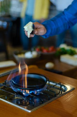 El chef está cocinando huevos en mantequilla para el desayuno. De poca profundidad de campo.
