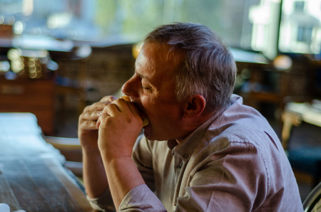 The Man with pleasure bites an appetizing burger in a steak house restaurant.