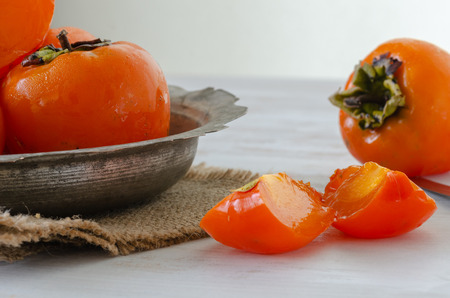 Ripe persimmons in a copper bowl on a white wooden table,close up, 스톡 콘텐츠