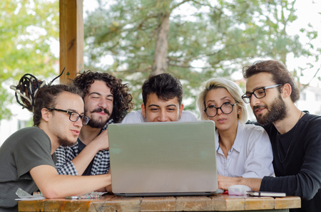 A group of young laptops working in the park.They all looking at the screen. 免版税图像