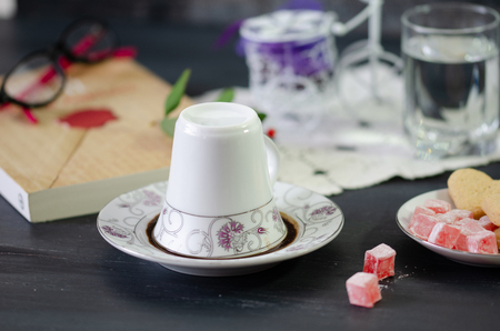 Turkish Coffee in White Porcelain Cup and Turkish Delight.Single overturned coffee cup on the plate for coffee divination