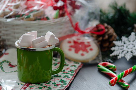 Hot chocolate with marshmallows in a enamel cup and  christmas cane sugar on Christmas decoration. Reklamní fotografie