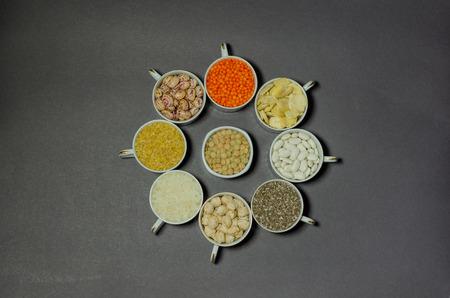 Vegan protein source. Legumes - lentils, chickpeas, beans, internal pods, bulgur, chia seeds  on black background. Top view copy space.