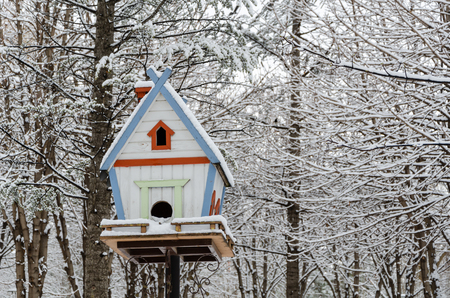 Wooden birdhouse hanging outdoors in winter covered with snow