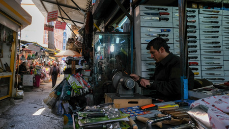 Eskisehir,TURKEY-January 14,2016: Man is grinding on abrasive cutting and knife-sharpening stones at Cutlers Bazaar