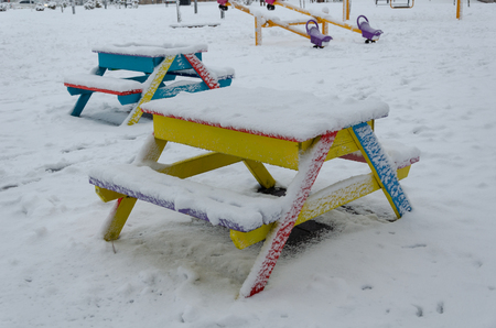 Children playground covered with snow in winter