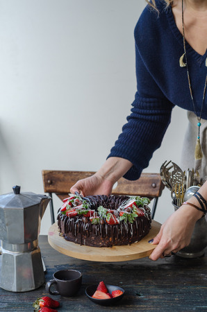 Woman brings strawberry cake to the table.