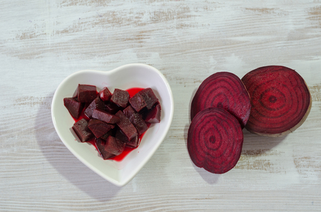 Slices of beets and boiled beet are on wooden table.Top view Banco de Imagens