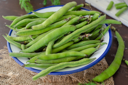 Fresh broad beans over wood background, selective focus Stock fotó