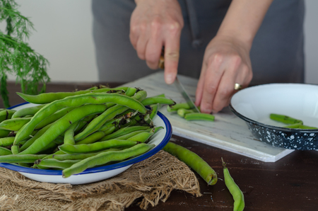 Woman is preparing to cook broad beans at the kitchen.