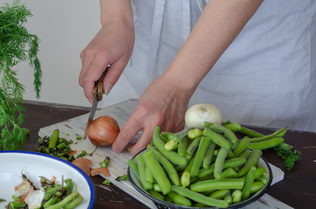 .Woman is chopping onions for cooking on the table..There are fresh broad beans and onion on the table. Stock fotó