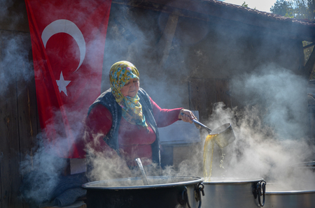 Seyitgazi,Eskisehir,TURKEY-October 15,2016: Old lady is simmering sugar beets in cauldron to make molasses. And control the consistency of molasses. Editorial