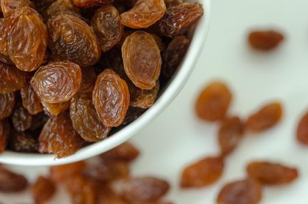 Bol avec des raisins secs sur fond blanc, vue de dessus. Alimentation saine avec des fruits