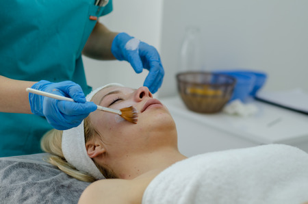 Beautiful woman having a facial cosmetic scrub treatment. Esthetician is cleaning blackheads. Anti-aging, facial skin care and luxury lifestyle concept. Imagens