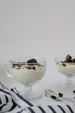 Layered dessert or Magnolia with  cacao biscuit cake and cream cheese of pudding on a white background. Stok Fotoğraf