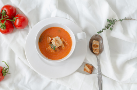 Bowl of tomato soup with croutons and fresh thyme on white background.
