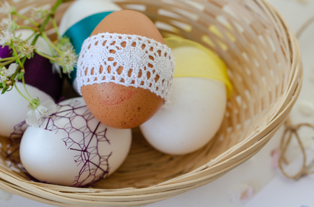 Fancy eggs are in the basket on white background. Easter concept